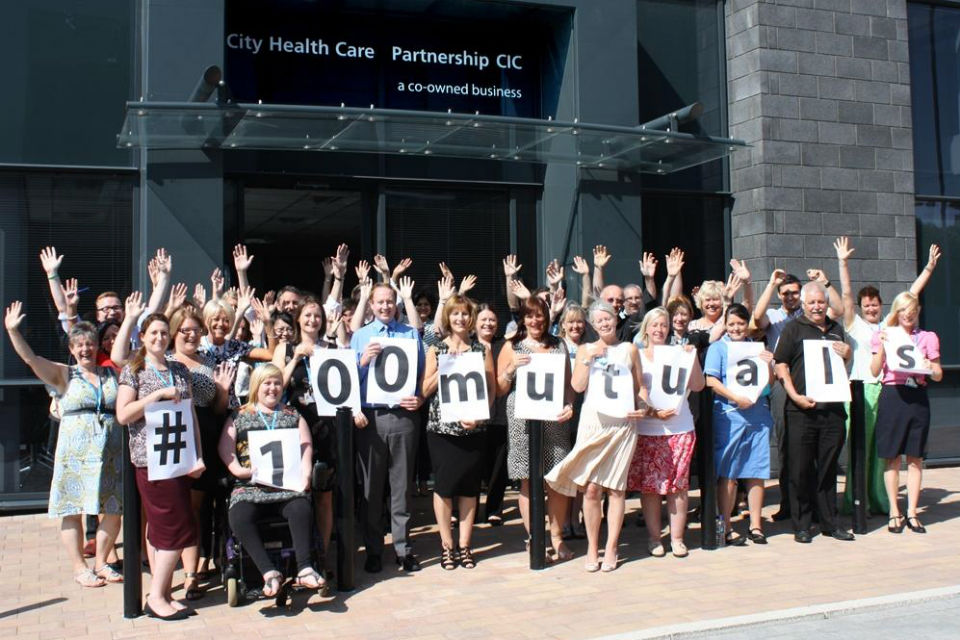 staff from a mutual society waving and holding a banner reading '#100 mutuals'