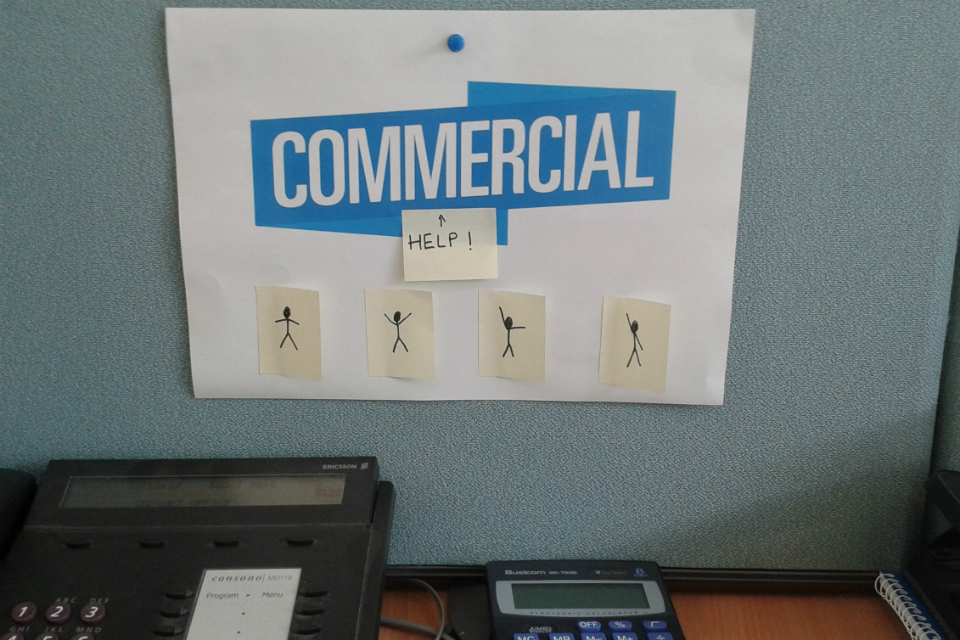 a sign saying 'commercial' with post-it notes reading 'Help' underneath