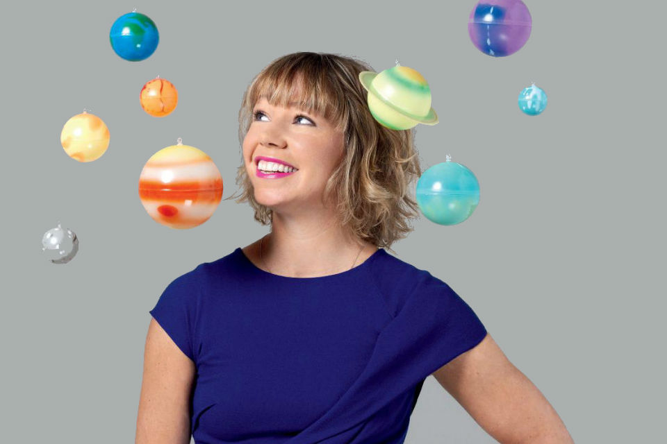 Photo of Dr Alice Bunn surrounded by planets from a model solar system