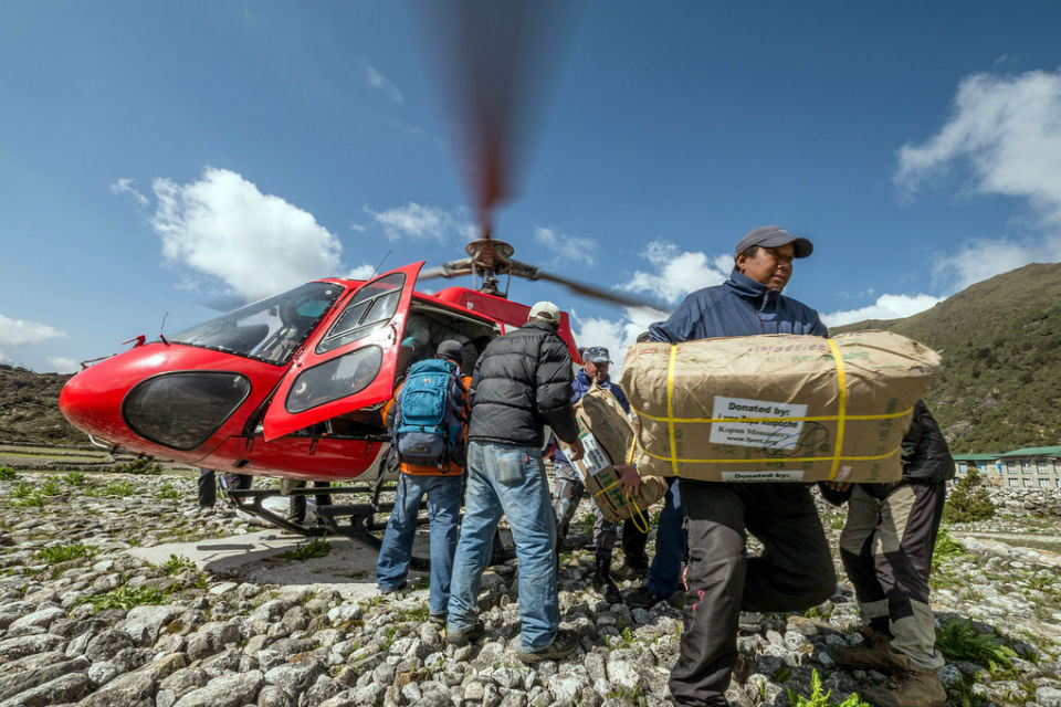 Aid workers unloading aid packages from helicopter in Nepal