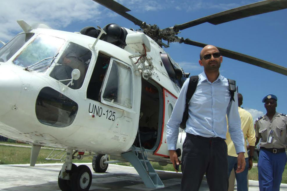 Mo Desai of DFID, with helicopter and overseas officials behind.