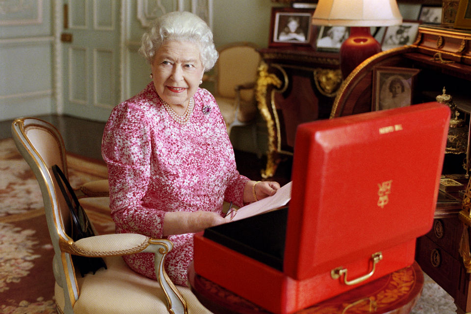 The Queen at her desk holding papers from open Red Box on desk