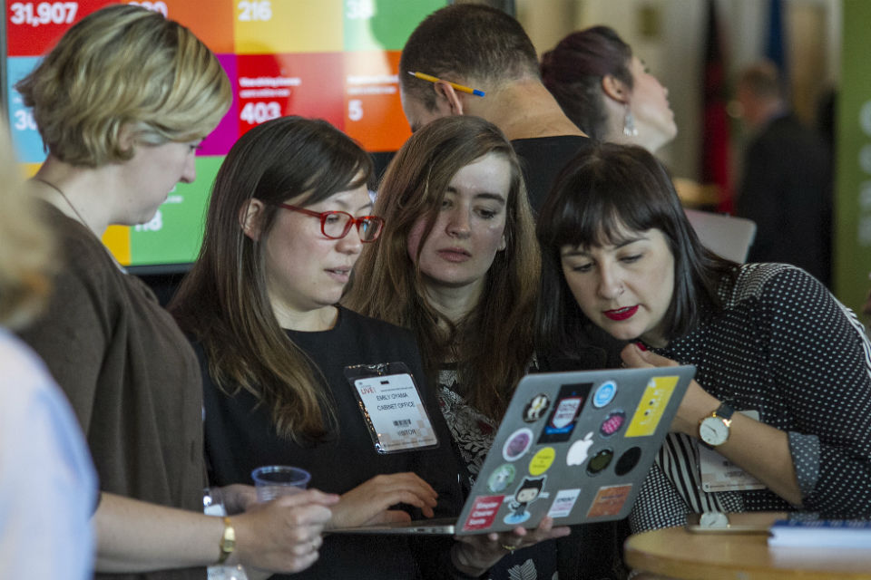 Delegates huddled around a laptop at the GDS stand Civil Service Live: Edinburgh