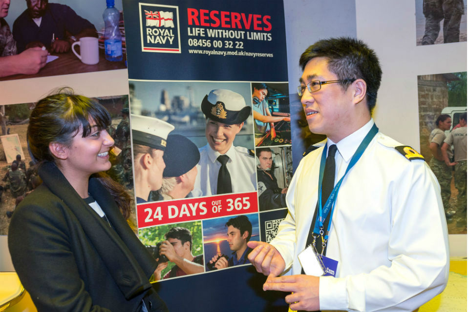 Royal Naval Reservist (right) explaining Reserve Forces to a female visitor at the Reserves Experience