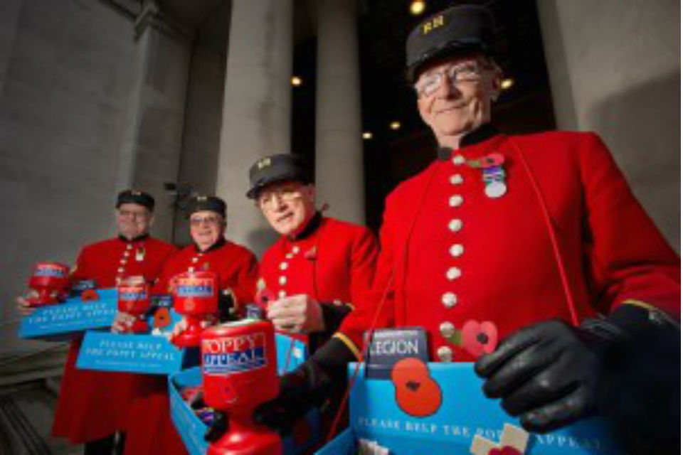 Four Chelsea pensioners in full uniform with British Legion poppy trays and collection boxes.