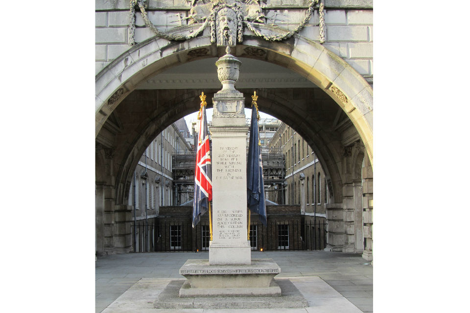 Memorial column, with urn atop, flanked by two flags, and arch, part of Somerset House, behind