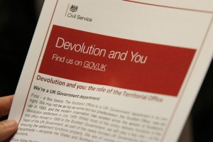 Tip of fingers of a hand holding booklet, showing title 'Devolution and You'