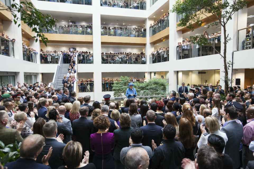The Queen, in blue, centre, addressing large audience of civil servants in atrium at Home Office building.