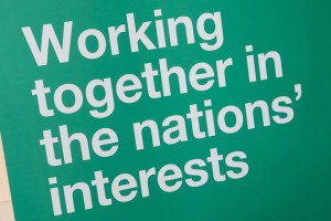 Banner with legend: Working together in the nations' interests