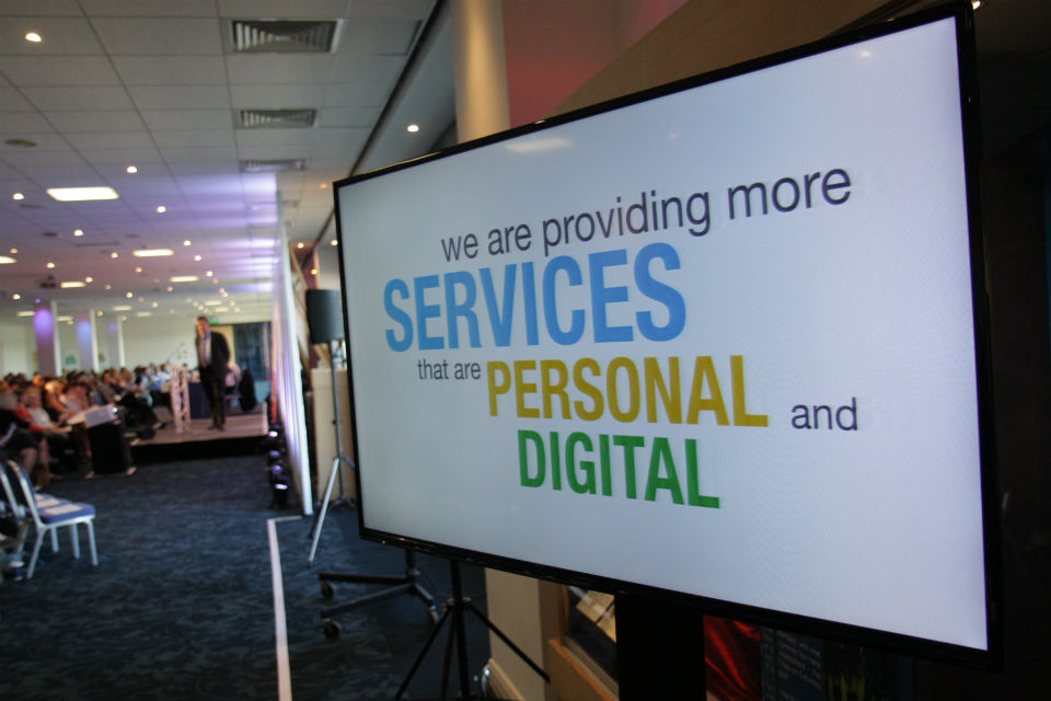 "Screen with slide ""we are providing more services that are personal and digital"" with speaker addressing audience in background"