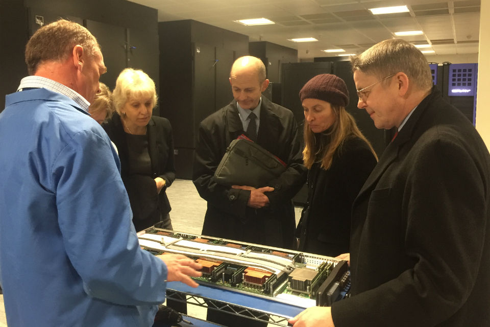 Jeremy Heywood, right, being shown computing equipment by a blue-overalled technician, while four others, three women and a man, look on.