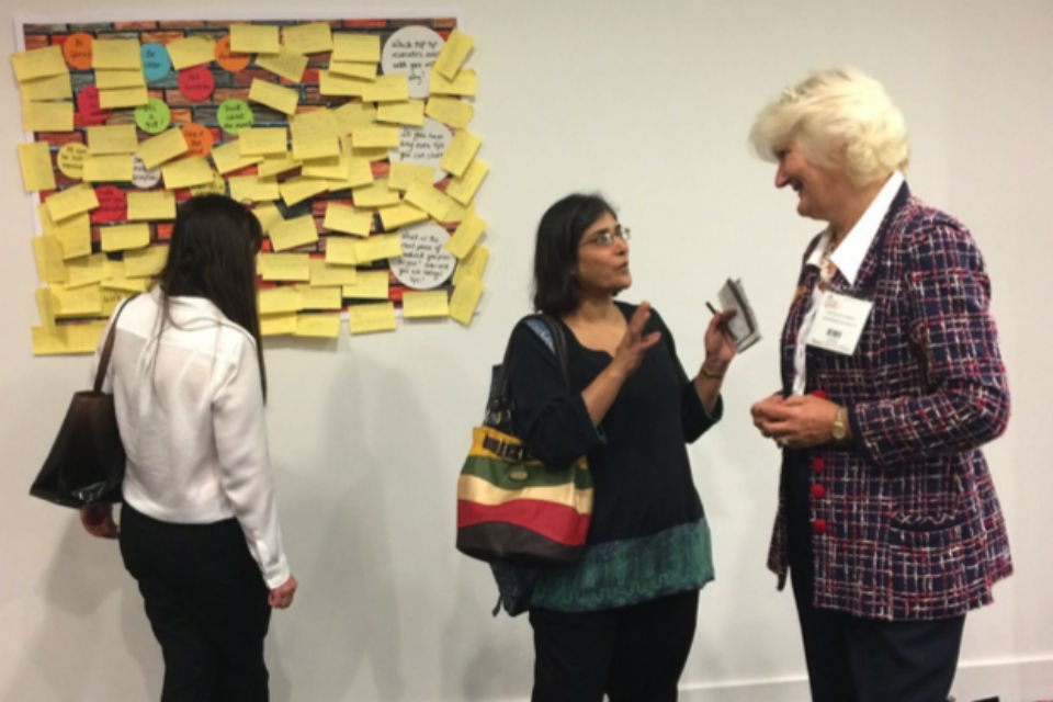 Felicity Harvey, right, speaking to a delegate at CS Live, with another perusing notes on a board back left.
