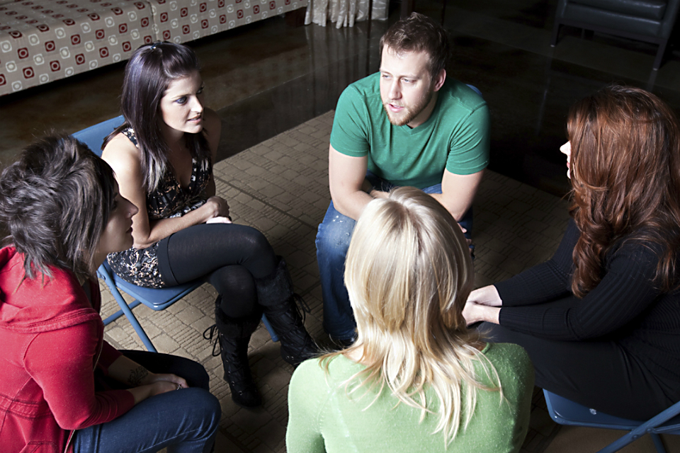 Photo of a counselling group talking, consisting of 5 young people sat in a circle, chatting