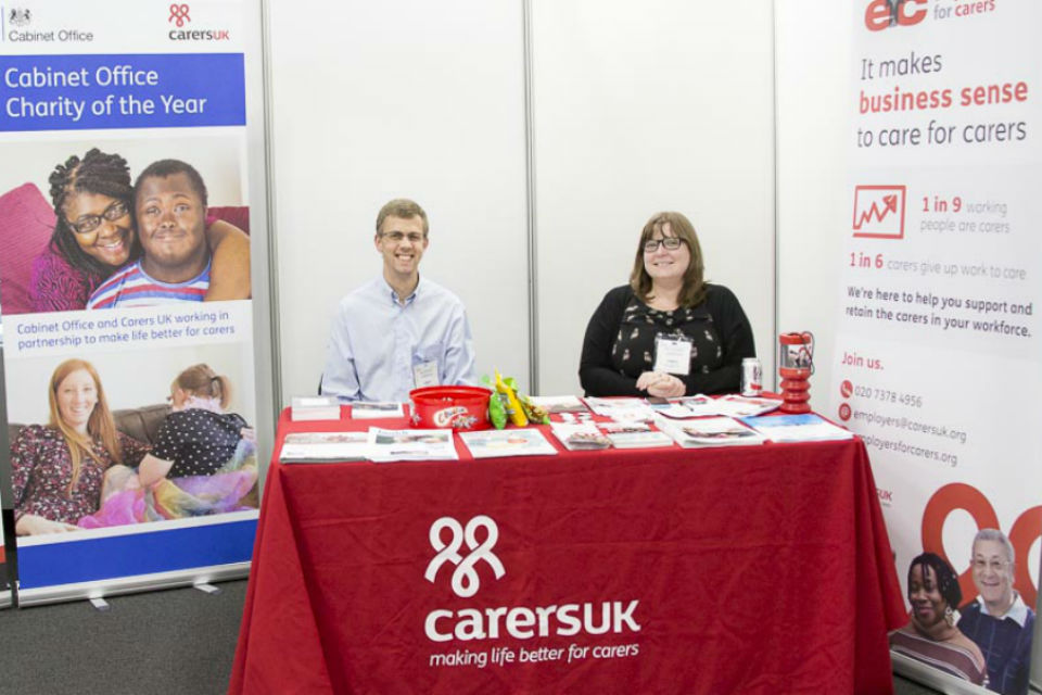 Man and woman seated behind red-clothed Carers UK stand at exhibition, flanked by display stands.