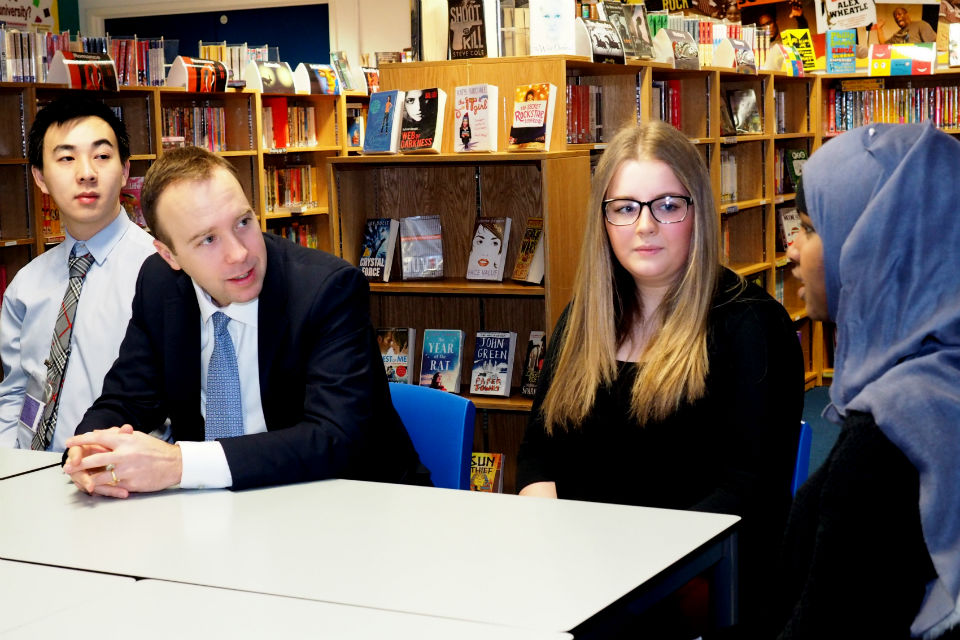 Matthew Hancock, second left, flanked by a male student (left) and a female student (right), listening to a third student, extreme right