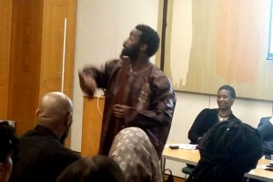Poet and storyteller performs in front of seated audience
