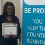 Woman holding certificate next to banner