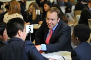 Man talking seated at table to three schoolchildren