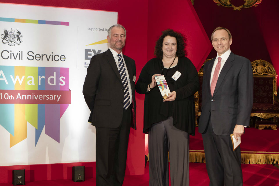 Woman with award flanked by two men with Civil Service Awards banner to their right