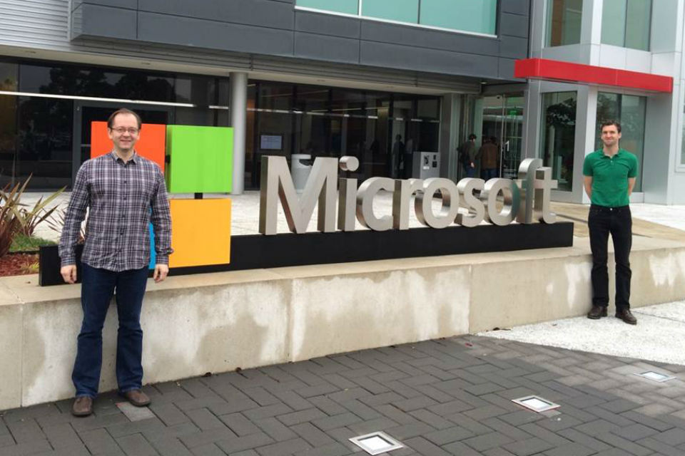 Two men standing by Microsoft sign