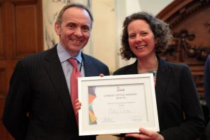 John Manzoni left and Katy Owen with framed award