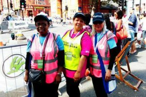 Three women in high vis jackets and hats