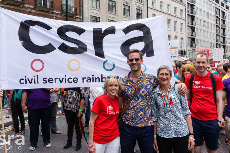 People pose in front of CSRA banner