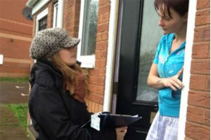 Woman in hat with clipboard speaking to another woman on their doorstep