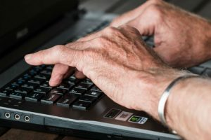 Image of two hands on a computer keyboard