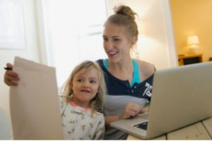 Young girl showing drawing to woman using laptop
