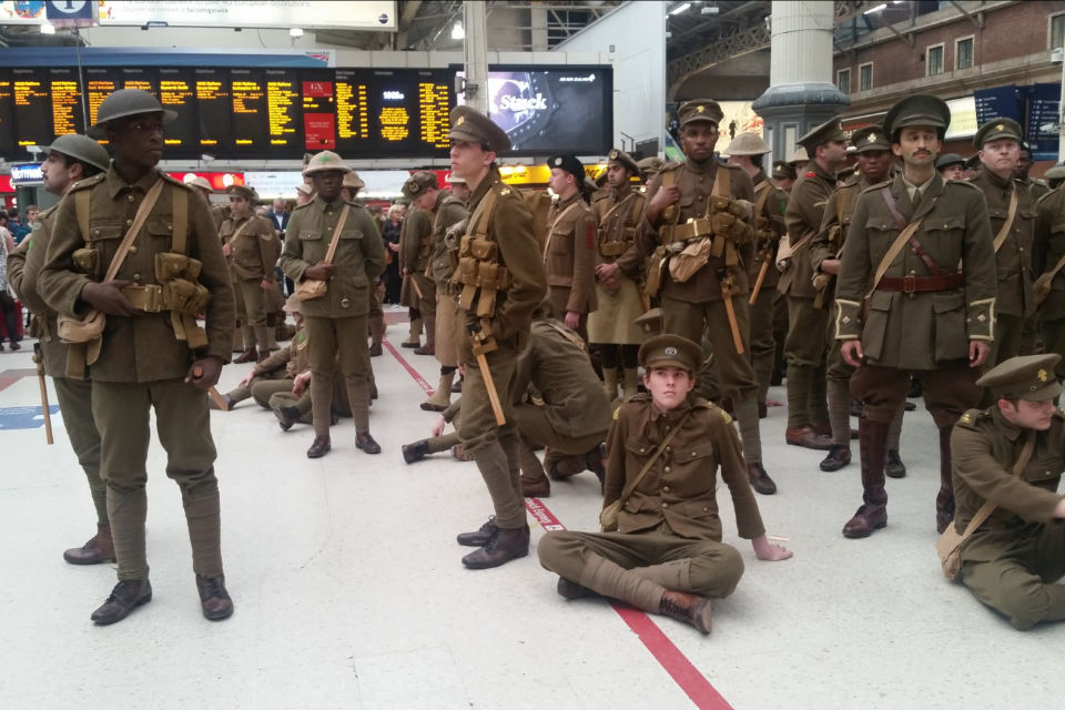Men in WWI uniforms at a station