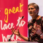 Woman speaking at lectern with banner behind with legend 'A great place to work'