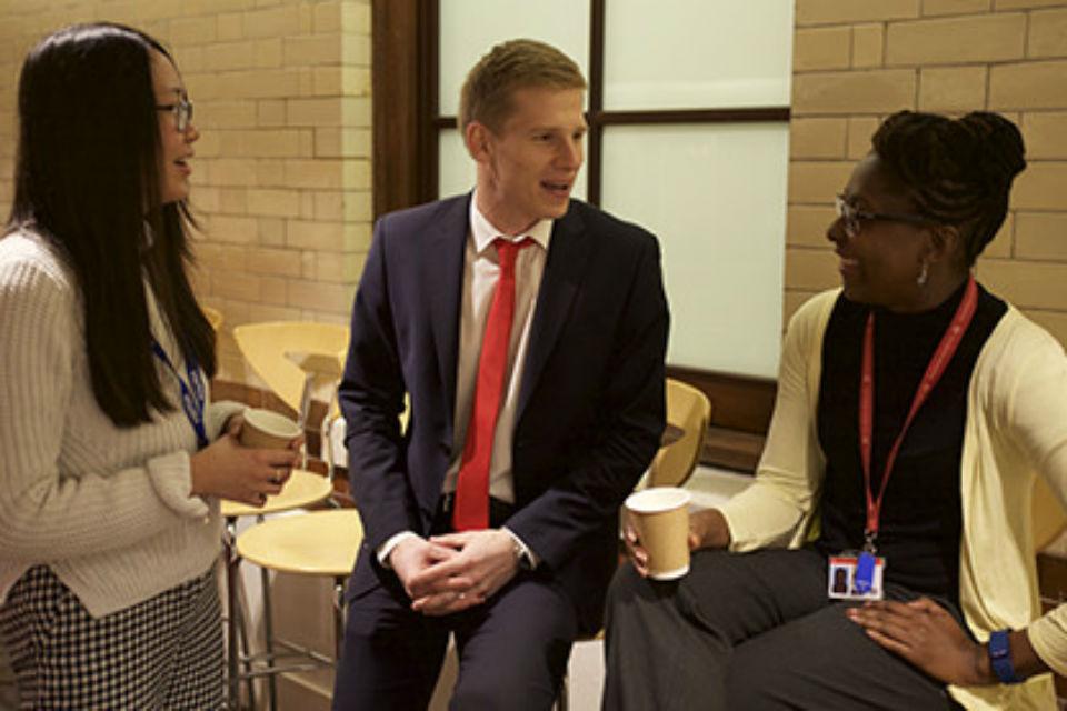 Man in suit and tie between two women