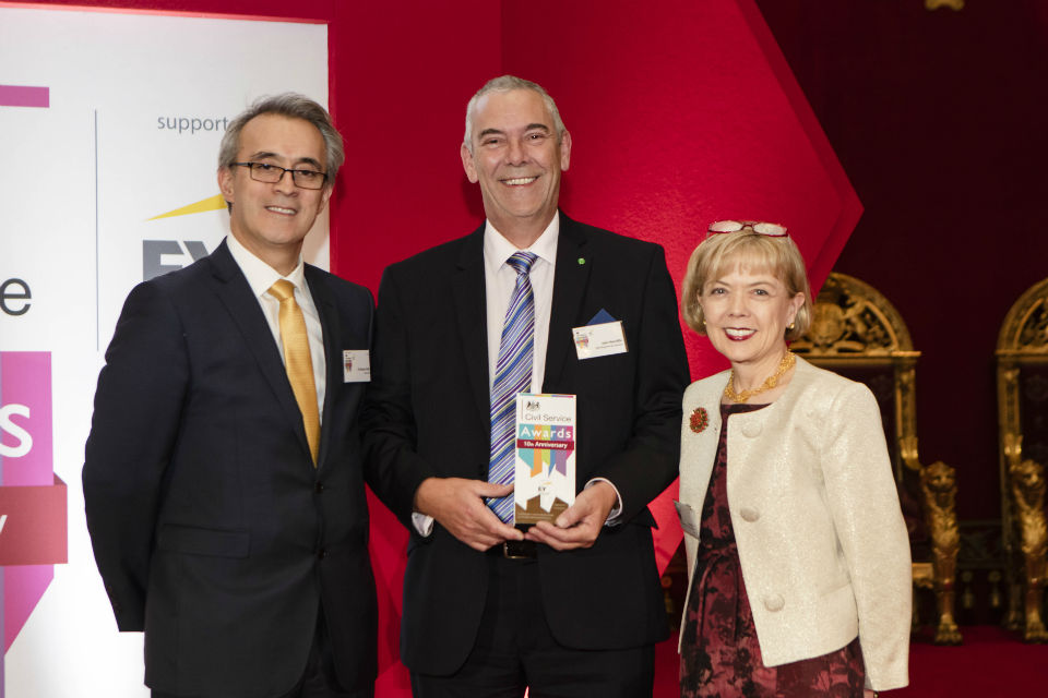 Man centre with award, flanked by man and woman