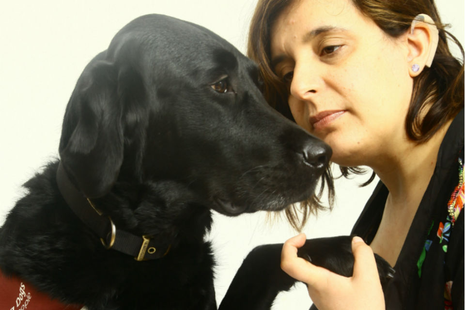 Woman holding paw of black labrador dog