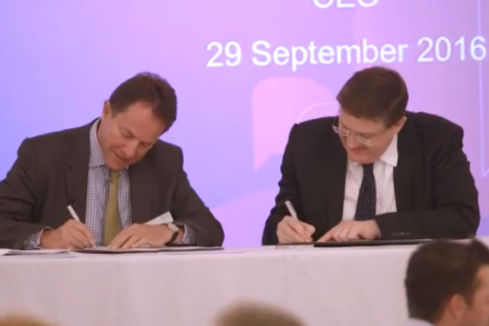 Two men signing documents