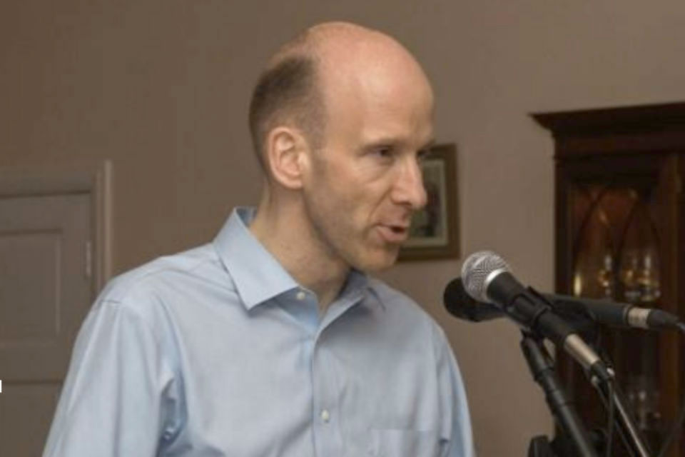 Bald man in blue shirt giving speech with microphones