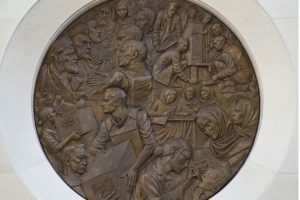 One face of bronze medallion surrounded by stone