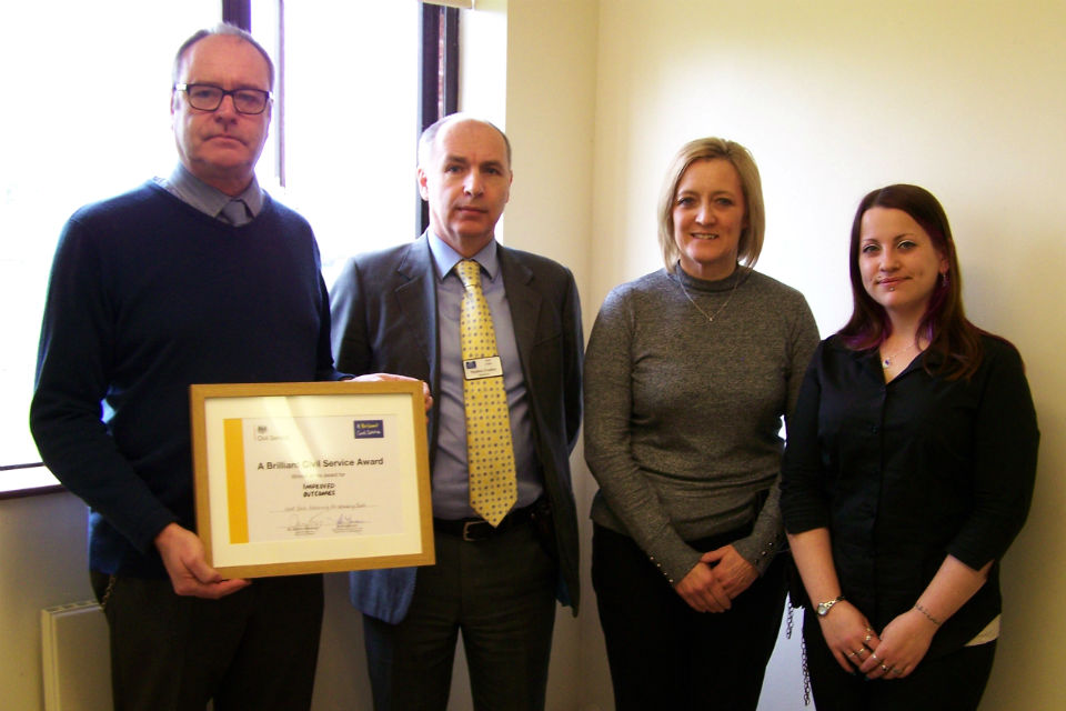 Two men and two women in a line, one holding framed award certificate