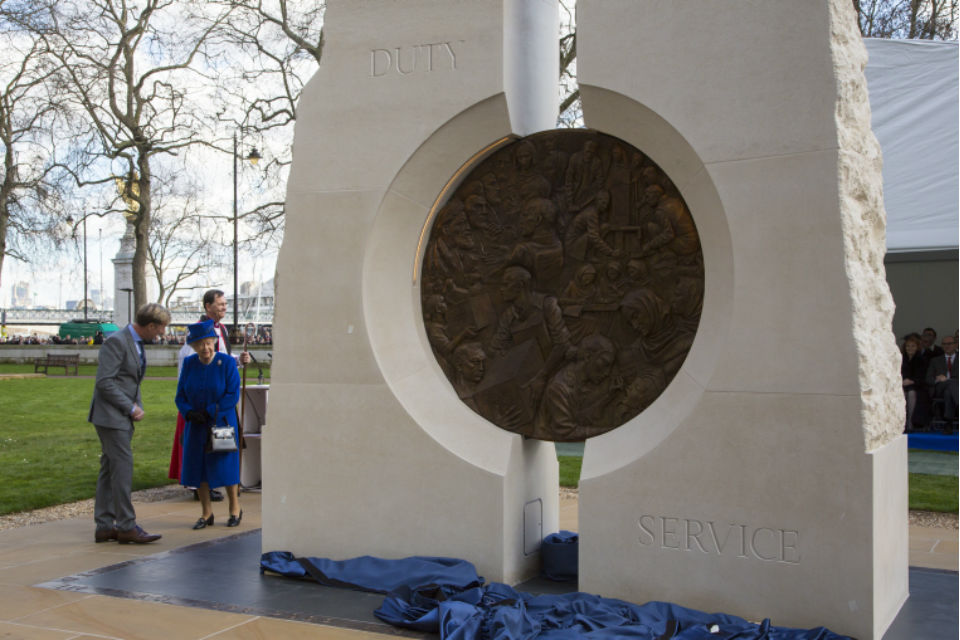 The Queen with man in suit and clergyman with memorial sculpture