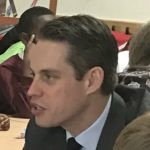 Man in suit, collar and tie speaking in primary school classroom surrounded by children.