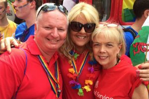 Man and two women at Pride event in red shirts