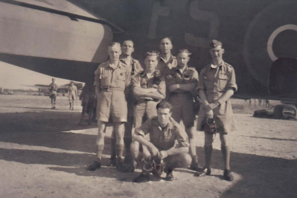 Britiish World War II air crew next to plane