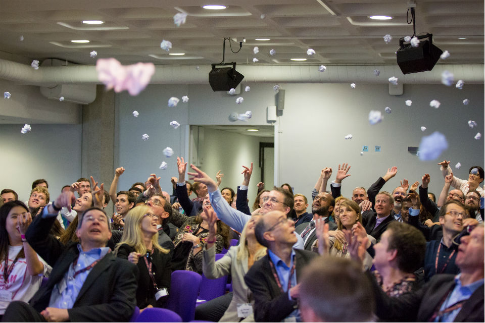 People in conference throwing crumpled post-it notes in the air