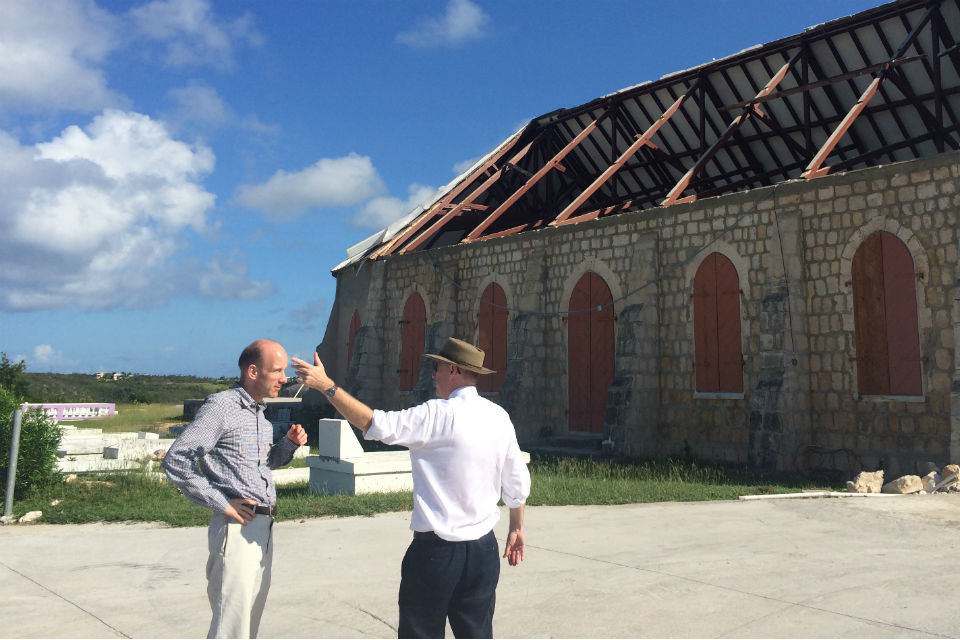 Two men talking in front of storm-damaged building