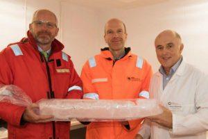 Three men holding ice core sample