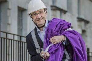 Man in hard hat with purple flag