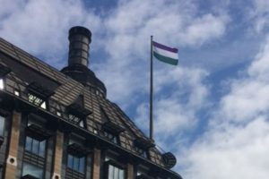 Women's suffrage flag flying from mast over building