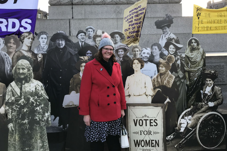 Woman in Trafalgar Square surrounded by cut-outs of women's suffrage campaigners