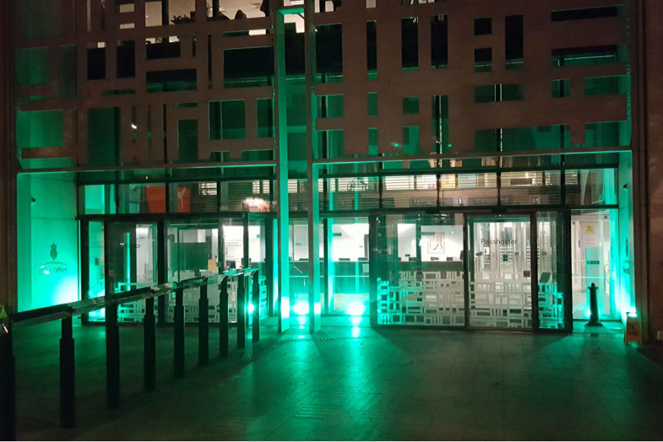 Exterior of building bathed in green light